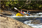 Two people white river rafting down rapids in a t...