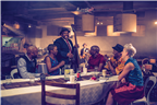 Group of friends sitting at a table in a jazz clu...