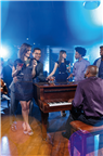 People standing around a piano in a jazz club in ...