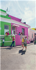 A UK couple walking past the colourful Bo-Kaap ho...