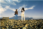 A young couple taking photos on Robben Island wit...