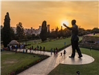People walking around the Nelson Mandela statue a...