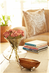 Flower vase, a wooden bowl and books make up the ...