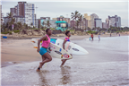 Two women running into the sea with surfboards