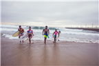 People walking with surfboards along Durban beach