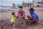 Parents building a sand castle with their child a...