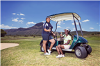 Two women drinking champagne in a golf cart