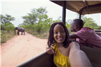 A woman taking a selfie on a game drive with an e...