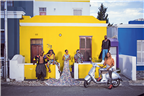 Fashionable people standing outside a colourful h...