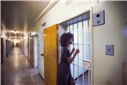 A woman looking into a cell on Robben Island