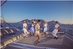 People dressed in white dancing on a yacht