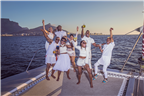 People dressed in white toasting on a yacht